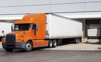 orange semi truck by the door of warehouse